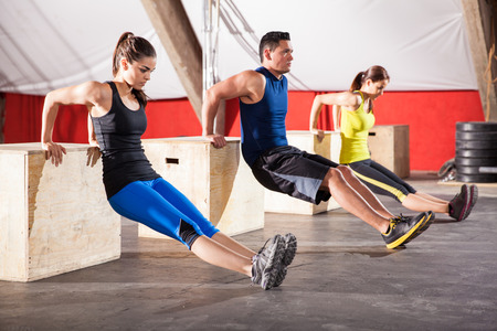 Group of young people working out their arms using boxes in a crossfit gym photo