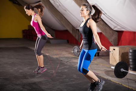 saltar la cuerda: Chicas atl�ticas Pretty utilizando cuerdas para saltar de su entrenamiento en un gimnasio crossfit Foto de archivo