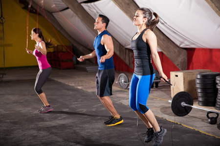 saltando: Grupo de gente atl�tica utilizando cuerdas para saltar de su sesi�n de ejercicios en un gimnasio de entrenamiento cruzado