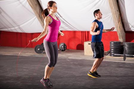saltar la cuerda: Hombre joven y mujer cuerdas de salto, como parte de su entrenamiento en un gimnasio crossfit