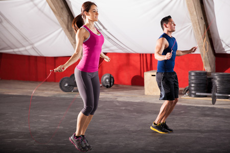 Young man and woman jumping ropes as part of their workout in a crossfit gym photo