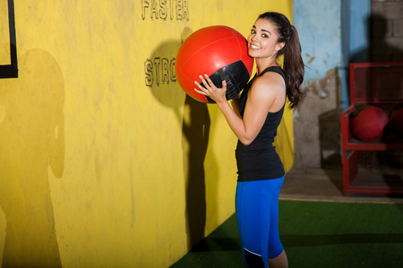 Beautiful young brunette working out with a medicine ball and smiling in a crossfit gym