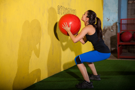 Cute girl working out by throwing a medicine ball to a wall in a cross-training gym photo