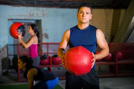 Stattliche lateinische junger Mann mit einem Medizinball in einem Fitness-Studio crossfit Standard-Bild