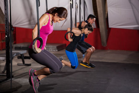 Group of people trying to pull their weight up using gymnastic rings in a cross-training gym photo