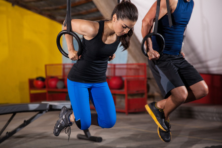 pull up: Athletic man and woman doing some pull up exercises in the gymnastic rings in a crossfit gym Stock Photo