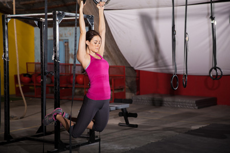 pull up: Pretty Hispanic woman working out in the gymnastic rings in a cross-training gym