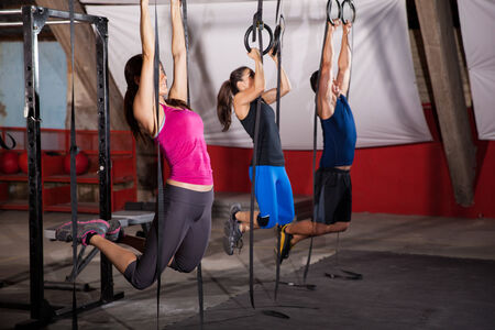 Group of three people pulling their weight up in the gymnastic rings in a crossfit gym photo