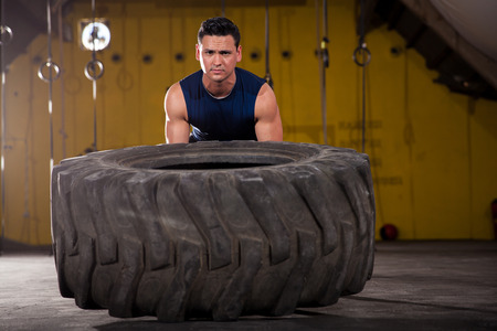 Athletic young man lifting a big tire as part of the workout of the day in a crossfit gym photo