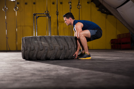 Men exercise: Young man about to flip a tire during his workout at a cross-training gym
