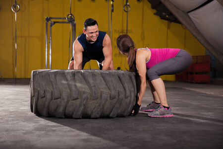 Charming young man giving a woman some tips on how to flip a tire in a cross-training gym photo