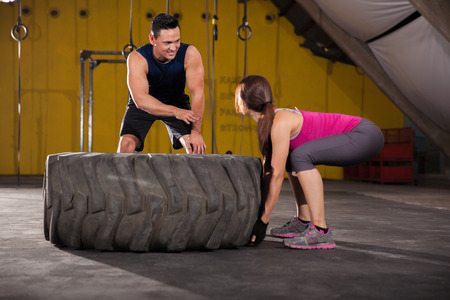 Athletic young woman getting some instructions on how to flip a tire in a crossfit gym photo