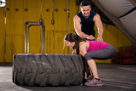 Handsome trainer showing the proper form for flipping a tire in a crossfit gym Stock Photo - 28495394