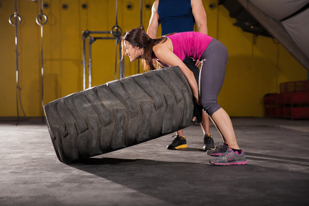 Young athletic brunette putting all her weight in to try and flip a big tire in a crossfit gym photo
