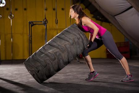 pesas: Hermosa mujer joven hispana mitad de mover de un tirón un neumático en un gimnasio de entrenamiento cruzado Foto de archivo