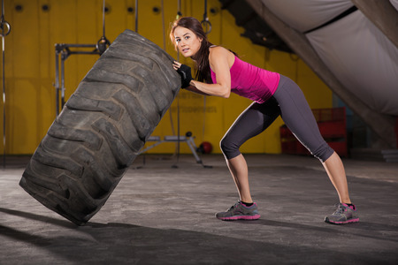 tire: Pretty brunette working out with a big tire in a crossfit gym