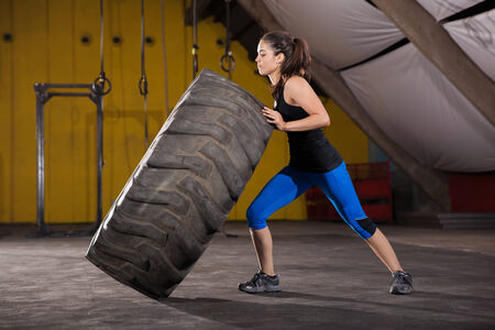 flipping: Strong brunette making almost no effort in flipping a big tire in a cross-training gym