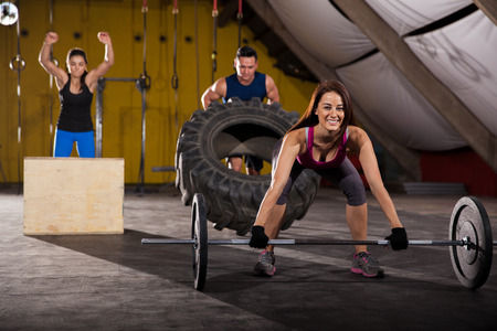 Happy people working out in a cross-training gym using weights, boxes, and tires photo