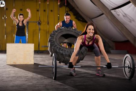 levantando pesas: La gente feliz trabajando en un gimnasio de entrenamiento cruzado usando pesas, cajas y neumáticos Foto de archivo