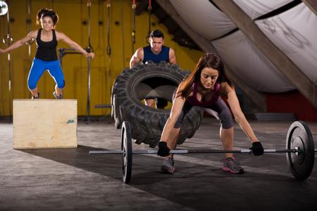 levantando pesas: Hacer ejercicio de levantamiento de pesas, saltar cajas, y mover de un tirón los neumáticos en un gimnasio crossfit