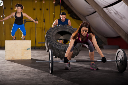 Working out by lifting weights, jumping boxes, and flipping tires in a crossfit gym
