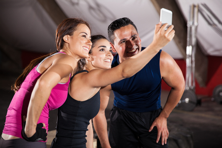 Happy athletic guys taking a group selfie after finishing their workout in a cross-training gym photo