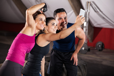 girl fitness: Strong and athletic Hispanic people taking a fun group selfie at a crossfit gym