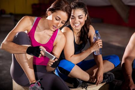 fitness: Amigos mensagens de texto Fêmea bonito e redes sociais em um ginásio crossfit Imagens