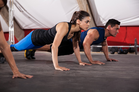 Beautiful young brunette doing some push ups with some other people at a crossfit gym