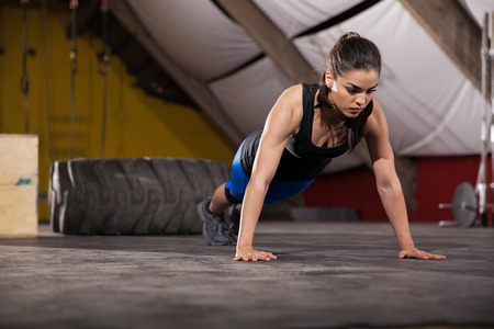 Athletic Latin woman doing push ups with extreme determination in a cross-training gym photo