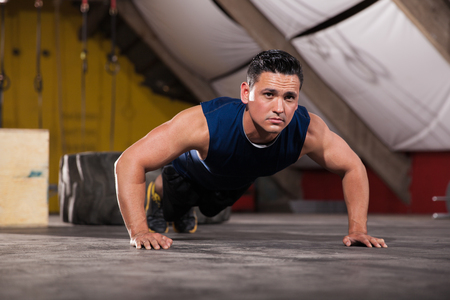 push: Athletic Latin man working out and doing some push ups in a cross-training gym Stock Photo