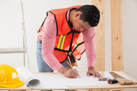 modifying: Hispanic contractor drawing and modifying a blueprint of a house