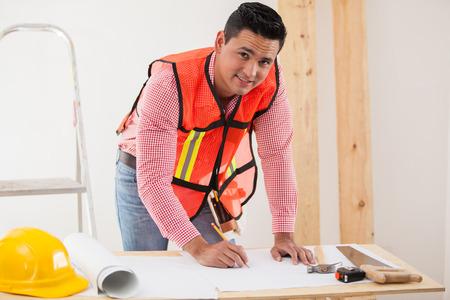 serrucho: Contratista joven hermoso que trabaja en un diseño de la remodelación de una casa