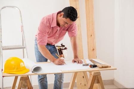 modifying: Young Latin man drawing and modifying a house design