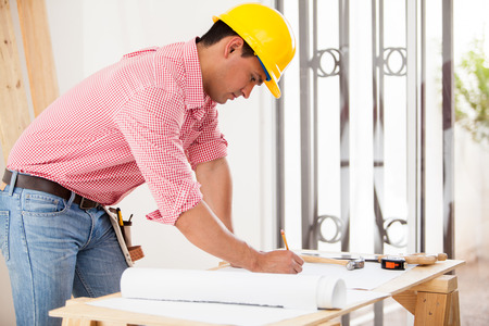 Handsome Hispanic engineer doing some design work and remodeling a house photo