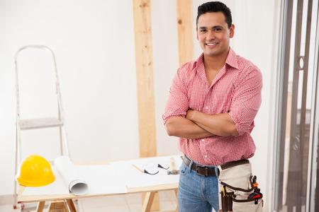 Portret van een aantrekkelijke jonge aannemer werken bij een huis en glimlachend