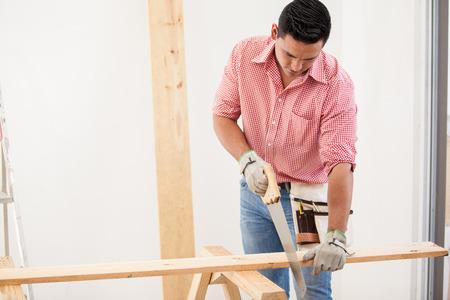 serrucho: Hombre hispano joven que hace algún trabajo de carpintería en una houes Foto de archivo