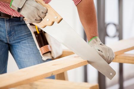 serrucho: Primer plano de un carpintero cortando unas tablas de madera para la construcción Foto de archivo