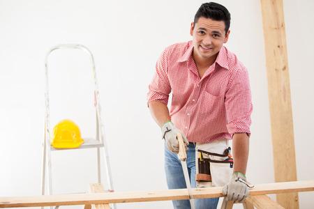 serrucho: Hermoso carpintero América cortando unas tablas de madera en el trabajo Foto de archivo