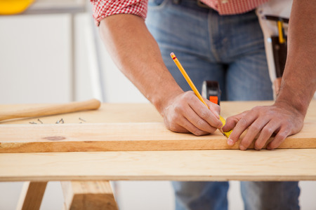 Closeup of a carpenter marking down some dimensions in a wood board Stock Photo