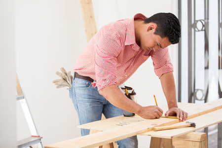 Handsome young carpenter using a tape measure to mark down a wood board dimensions before cutting it photo