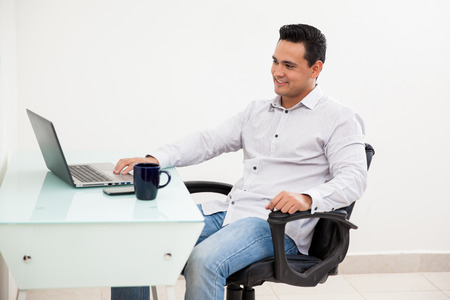Handsome Hispanic man working from home on his laptop and drinking coffee photo