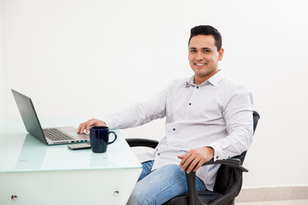 Attractive young man working at his office using a laptop computer and smiling photo