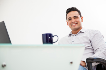 Portrait of a young Latin man working at his office and drinking coffee photo