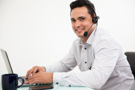 Handsome Hispanic man wearing a headset and taking a call from a customer at work