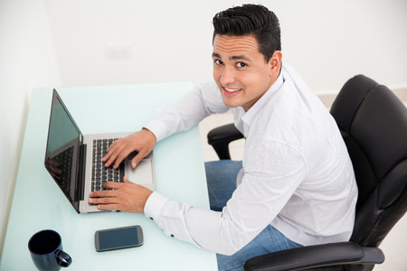 Portrait of a handsome young man working in an office using a laptop and drinking coffee photo