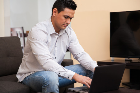 Young Latin man working from home using a laptop computer in the living room photo