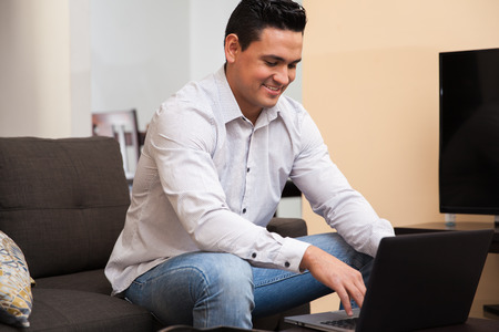latin man: Portrait of a good-looking young man using a laptop computer to work from home