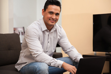 Handsome young man social networking on his laptop at home and smiling photo