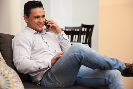 latin man: Handsome Hispanic young man talking on his cell phone while relaxing at home Stock Photo